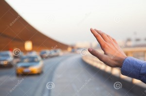 hand-traveler-hailing-taxi-outside-airport-31132306.jpg